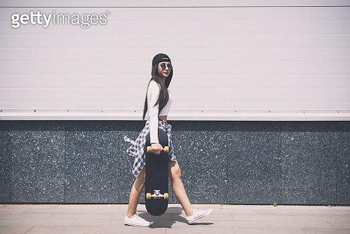 Young girl walking away with her skateboard and looking at the camera - gettyimageskorea