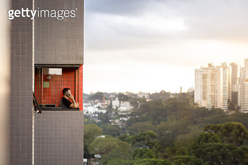Man talking on phone at home balcony - gettyimageskorea