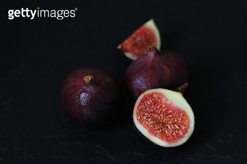 Close-up of well ripened figs, cut open to expose seeds and juicy innards. Still life composition on black background. - gettyimageskorea
