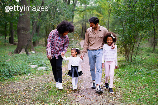 Happy family walking along a path in the woods - gettyimageskorea