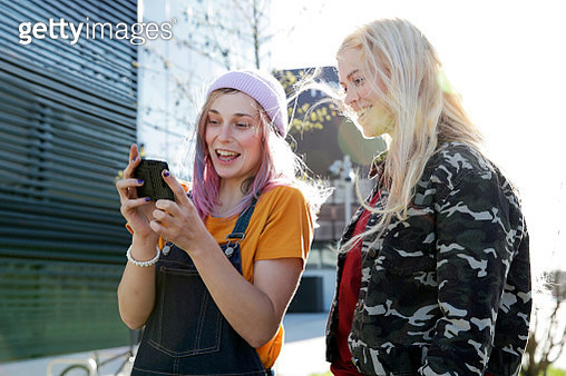 Young women talking and using mobile phone, walking along street, smiling and having fun - gettyimageskorea