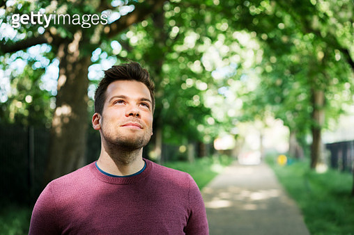 Man looking up, with sun on his face - gettyimageskorea