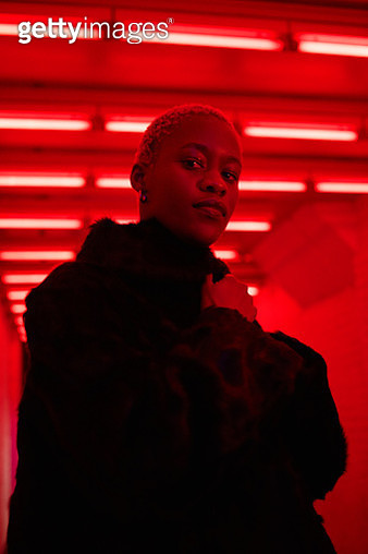 Portrait of young woman with blond short hair wearing black fur and white sweater infront of neon lights. - gettyimageskorea