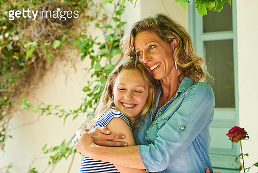 Portrait of a mature mother with her teenage daughter embracing and relaxing outdoors at home - gettyimageskorea
