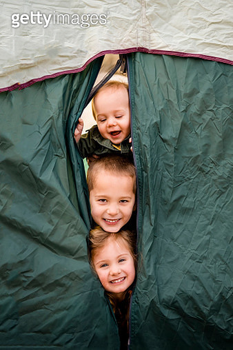 Three smiling children peek faces out of camping tent - gettyimageskorea
