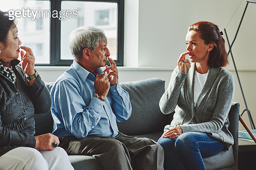Healthcare worker showing the pressure points to senior couple - gettyimageskorea