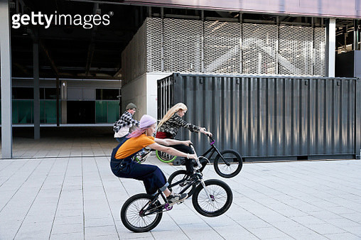 Three women cycling together in urban setting, side view, balance, skill - gettyimageskorea