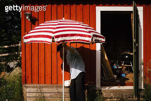 Man unfolding parasol in front of shed - gettyimageskorea