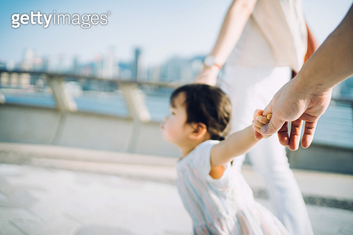 Cute little toddler girl holding her mother and father's hand strolling along the promenade against urban cityscape on a lovely sunny day - gettyimageskorea