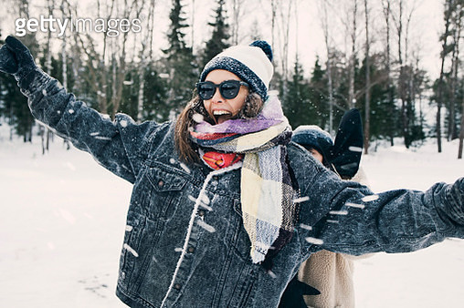 Happy woman enjoying with friend at snowy field - gettyimageskorea