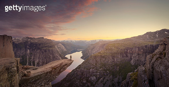 Panoramic of traveller looking out at landscape at sunset, Trolltunga, Norway - gettyimageskorea