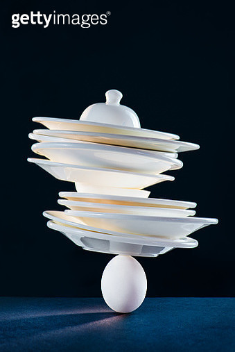 Stack of porcelain plates balancing on an egg, fragility concept with copy space - gettyimageskorea