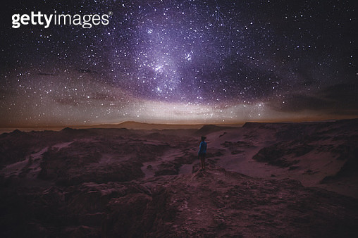Woman enjoying stargazing under the night sky with million of stars and Milky Way at beautiful canyon on Atacama Desert in Chile - gettyimageskorea