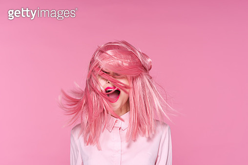 Woman on pink background with flying pink hair, portrait - gettyimageskorea