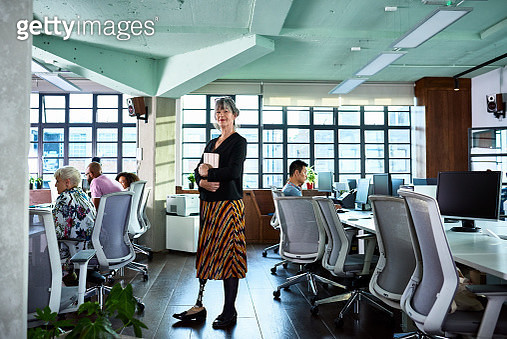 Female manager with above right knee amputation, looking at camera, cheerful and proud, multi racial team members in background, working with desktop computers, confidence and independence - gettyimageskorea