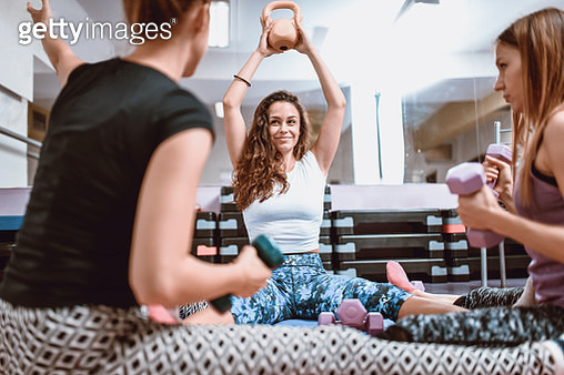 Female Athletes Working Out With Weights In Sitting Position At The Gym - gettyimageskorea