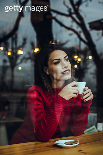Smiling young woman with cup of coffee behind windowpane in a cafe - gettyimageskorea