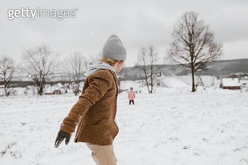 Boy and his little sister playing together in snow-covered landscape - gettyimageskorea