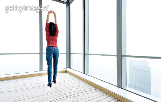Woman arms raised and looking through the window - gettyimageskorea