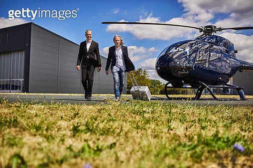 Two businessmen walking on runway with helicopter - gettyimageskorea