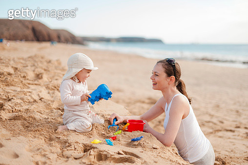 Mother playing with little daughter on the beach - gettyimageskorea