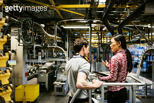 Mechanic and manager talking nearby a machine in a big printery about latest newspaper print - gettyimageskorea
