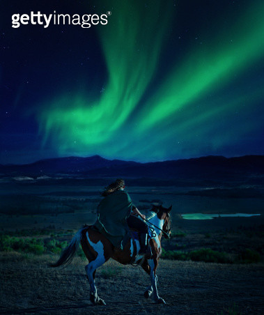 Woman on horseback gazes out at Northern Lights - gettyimageskorea