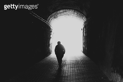 Rear view silhouette of a senior man walking towards the light at the end of the tunnel - gettyimageskorea