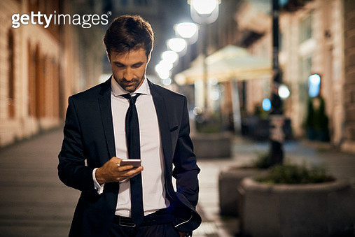 good looking businessman using smartphone after work in the city - gettyimageskorea