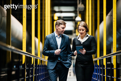 Two Business Person Walking A Dark Factory Hallway and talking about their latest projects - gettyimageskorea