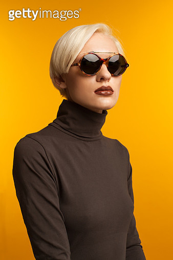 Portrait of blond girl wearing sunglasses and brown sweater. Shot in studio on yellow background. - gettyimageskorea