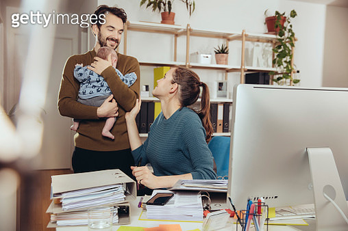 Smiling mother at desk looking at father holding baby in home office - gettyimageskorea