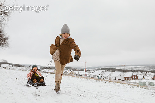 Boy pulling sledge with little sister in snow - gettyimageskorea
