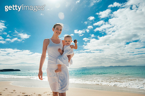 Mother walking with little daughter on the beach - gettyimageskorea