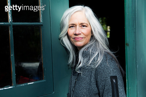 Woman with light, gray hair outside smiling. - gettyimageskorea