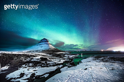 Northern lights in Mount Kirkjufell Iceland with a man passing by - gettyimageskorea