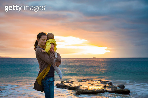 Mother holding little daughter on the beach at sunset - gettyimageskorea