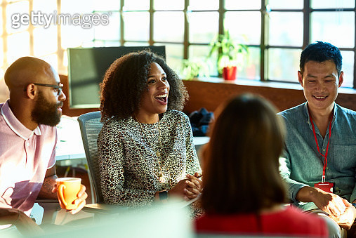 Mixed race woman smiling and laughing in relaxed team meeting - gettyimageskorea