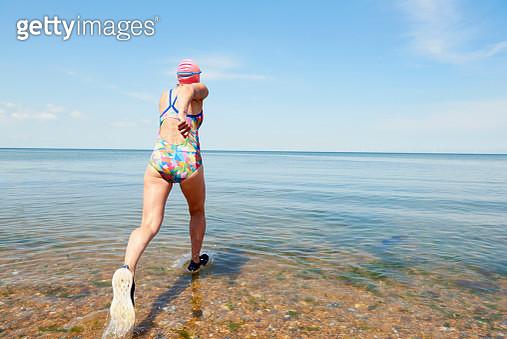 mature woman running into sea - gettyimageskorea
