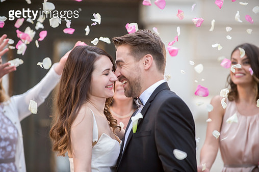 Friends throwing petals on wedding couple - gettyimageskorea