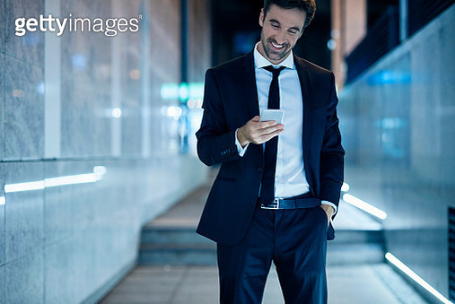 cheerful businessman using his smartphone after work at night - gettyimageskorea