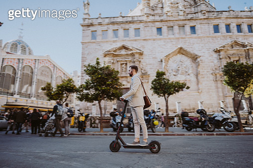 Man riding a motor scooter in Valencia on his way to work - gettyimageskorea
