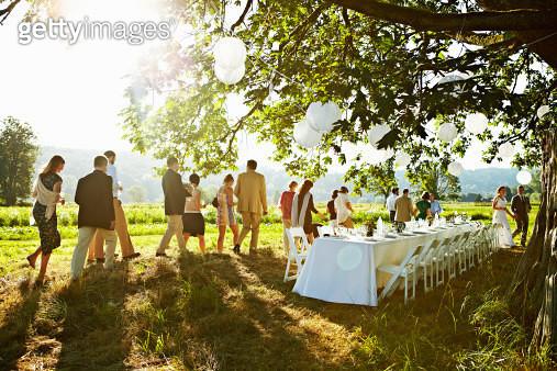Wedding party walking to table under tree in field - gettyimageskorea