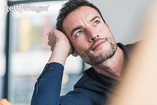 Mature man sitting in office, thinking, leaning head on hand - gettyimageskorea