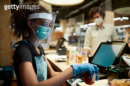 A grocery's cashier checking out products with a face shield - gettyimageskorea