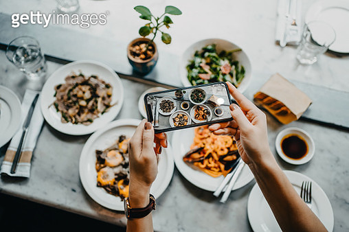 Overhead view of a woman's hand taking photo of freshly served food before eating it with smartphone in a restaurant - gettyimageskorea