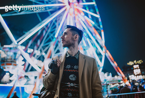 Attractive young man in warm, fashionable clothing at a fun fair in George Square, Glasgow, Scotland. Behind him in the background are the bright carnival lights of a Ferris wheel. - gettyimageskorea