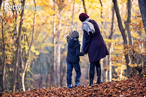 Mother and son in autumn forest. - gettyimageskorea