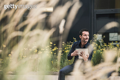 Businessman sitting outside, taking a break, drinking coffee, using digital tablet - gettyimageskorea