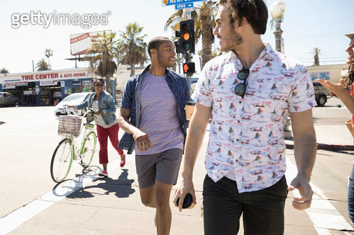 Friends crossing sunny California street on crosswalk - gettyimageskorea